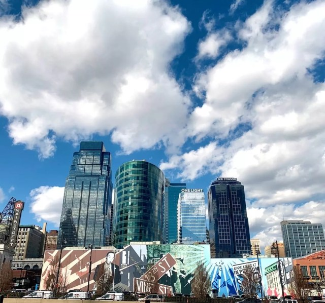 mural on wall with kansas city, mo skyline in back against bright blue sky with clouds photo by Instagram user @visitkc