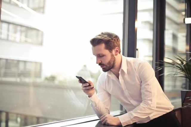 Man looking at smart phone near window. Photo by Instagram user @calllogic