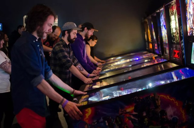 Group of people playing pinball machines at arcade Photo by Instagram user @groundkontrol