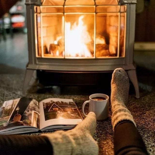 Person Relaxing with a Magazine and Hot Cocoa in Front of a Detached Fireplace. Photo by Instagram user @vanessa_hinds