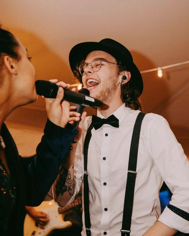 Party Guests Singing into Microphones at a Holiday Party. Photo by Instagram user @speechlessmusic