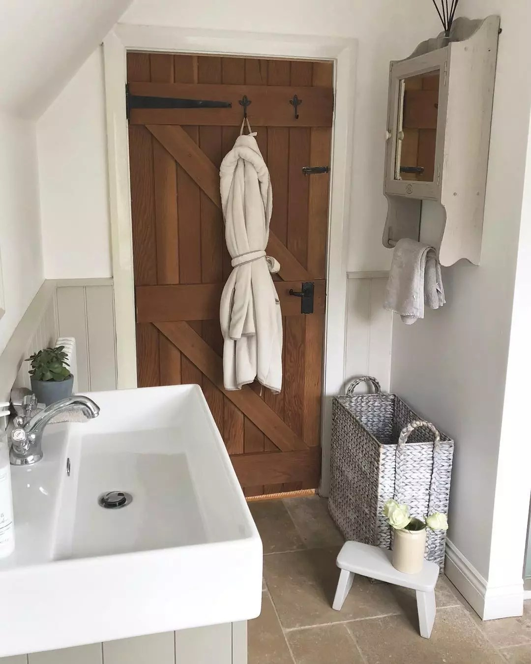Farmhouse-style bathroom with wooden barn door. Photo by Instagram user from_coast_to_country_home