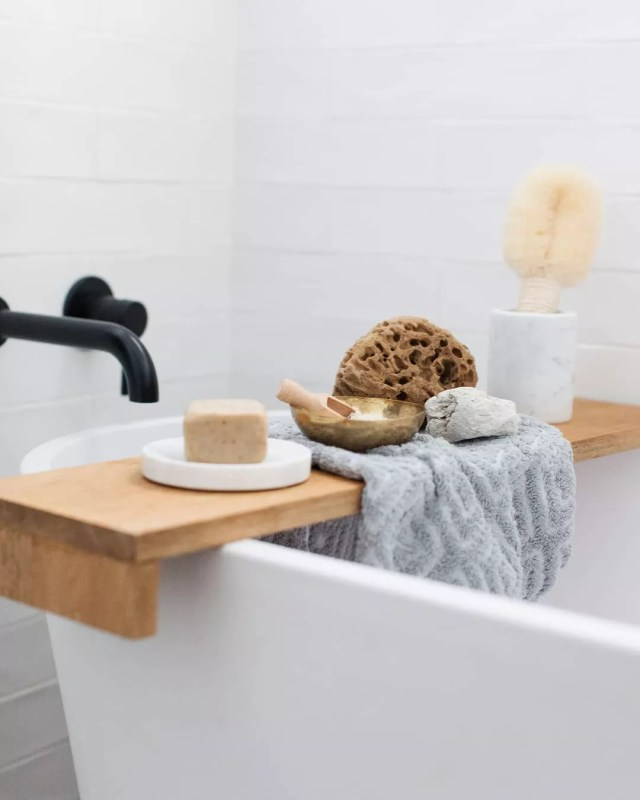 Bathtub shelf with loofas and sponges. Photo by Instagram user @stylecuratorau