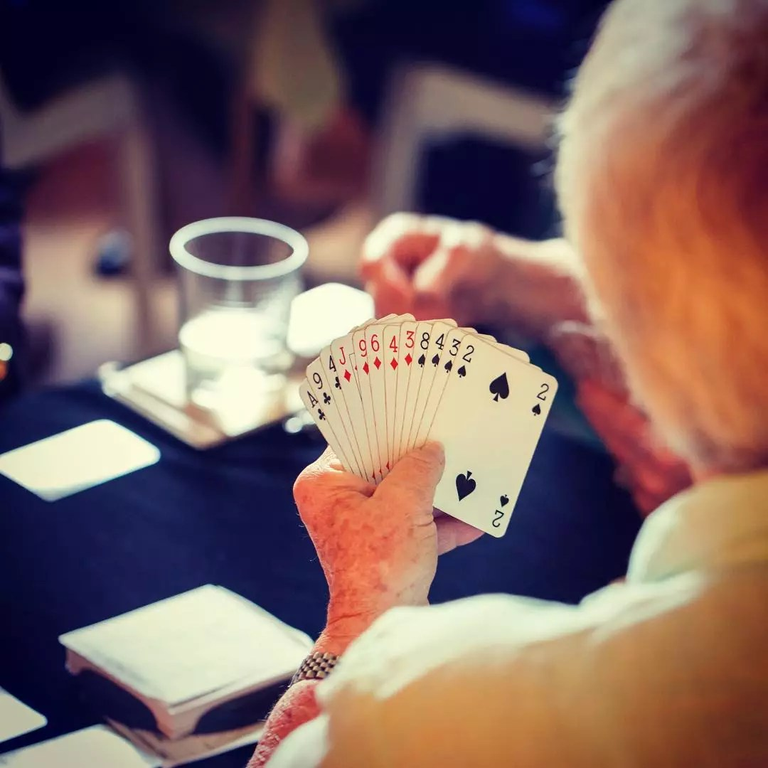 Elderly Woman Playing Cards. Photo by Instagram user @karunahospice