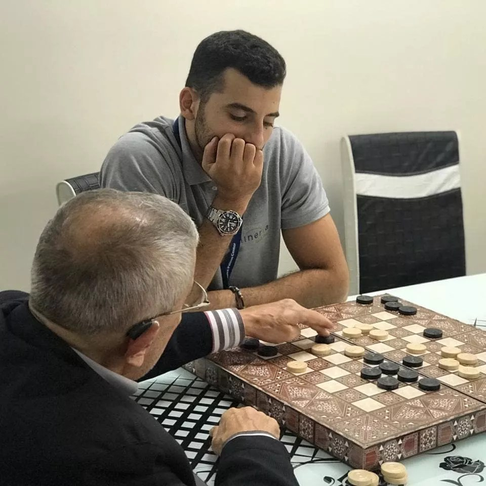 Elderly Man Playing Checkers with Young Man. Photo by Instagram user @minervaadultcare