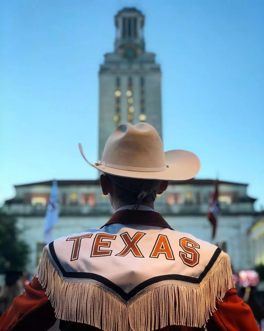 Member of UT band stands in front of UT Tower. Photo by Instagram user @utaustintx