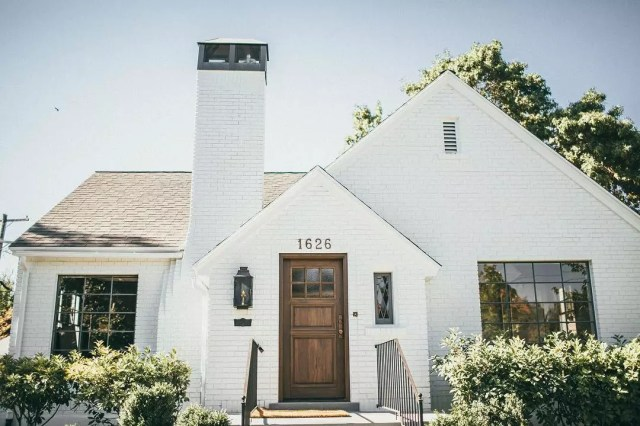 Front on single-family home with large chimney and white brick siding. Photo by Instagram user @annemariebarton