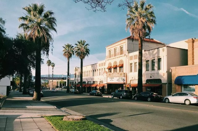 Movie theater between palm trees in Redlands, CA. Photo by Instagram user @ericwhedbee