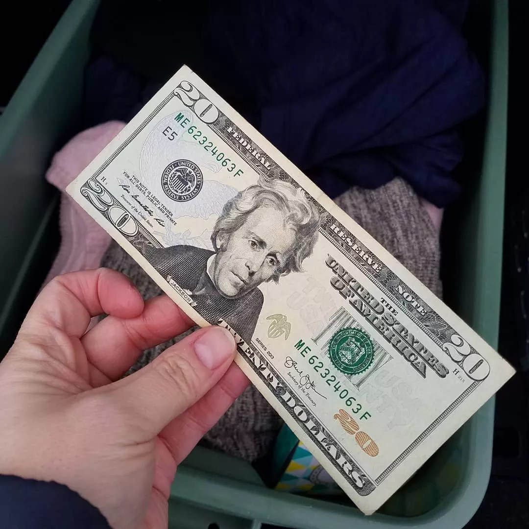 Hand Holding $20 Bill with Hamper of Old Clothes in Background. Photo by Instagram user @ksbudgetmom