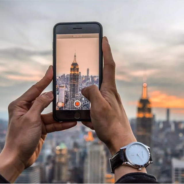 Man Using His Phone to Take a Photo of the Empire State Building. Photo by Instagram user @telestowatches