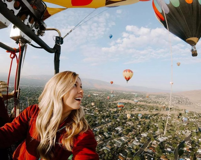 Thrilled Woman Riding in a Hot Air Balloon High Above the Ground. Photo by Instagram user @ashploussard