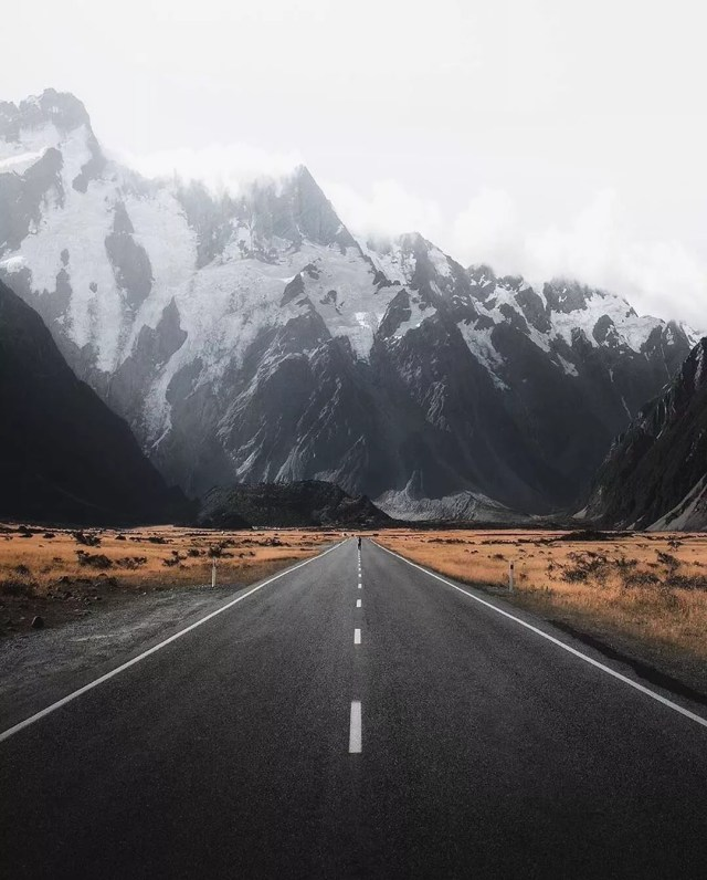 Open Road in Front of a Mountain Range. Photo by Instagram user @earth.all