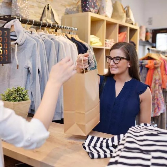 Customer Grabbing a Shopping Bag from an Employee. Photo by Instagram user @shopvanmall