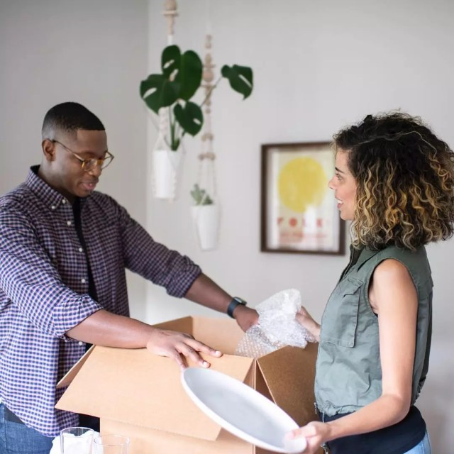 Couple Placing Unneeded Items into Donation Box. Photo by Instagram user @bellhopmoving