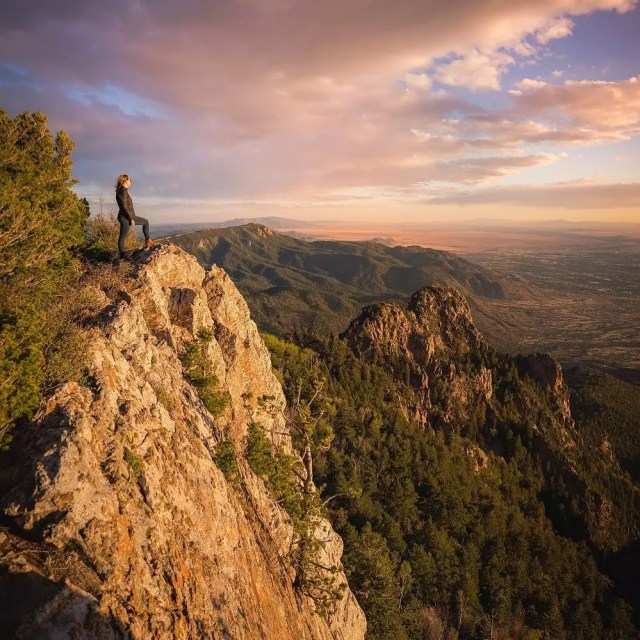 Woman looks down into a valley from the top of a mountain peak Photo by Instagram user @visitabq
