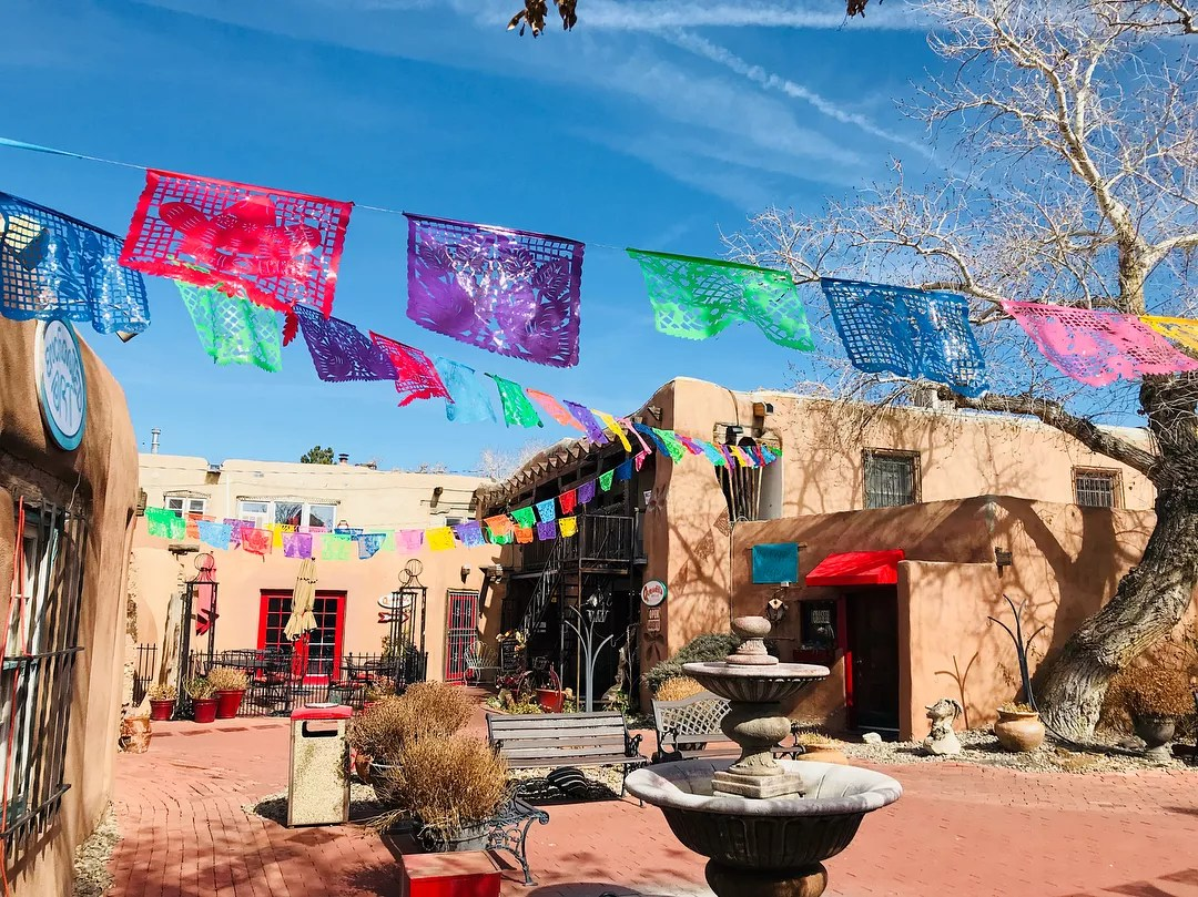 Courtyard adorned with colorful banners in Old Town Albuquerque. Photo by Instagram user @qhwinnie