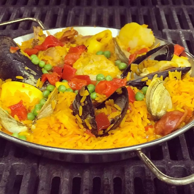 Closeup of pan of paella cooking on a grilltop. Photo by Instagram user @fornos_of_spain