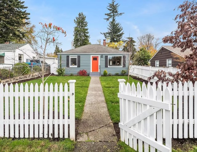 Grey house with an orange door and white picket fence in Greenwood, Seattle. Photo by Instagram user @parsonsteamseattle