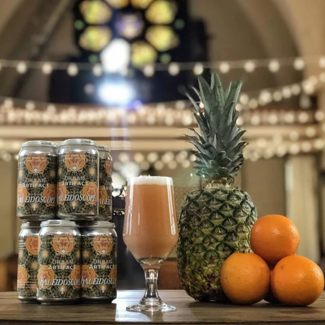 Chalice of beer next to cans and a pineapple at Urban Artifact in Cincinnati, OH. Photo by Instagram use @urbanartifactbeer