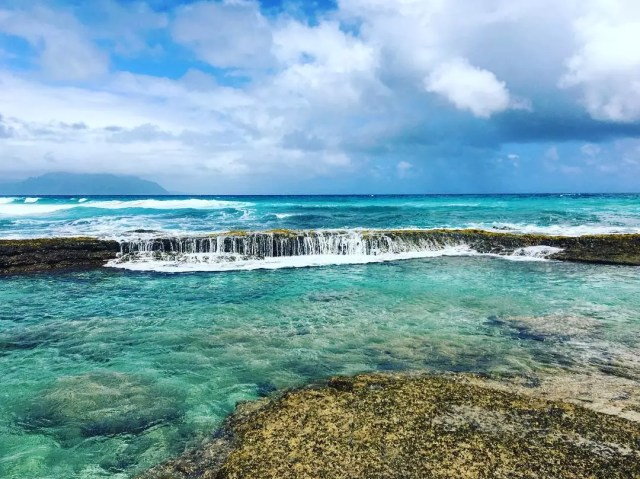 Crystal blue water fall in the ocean in Hawaii. Photo by Instagram user @hyperheather