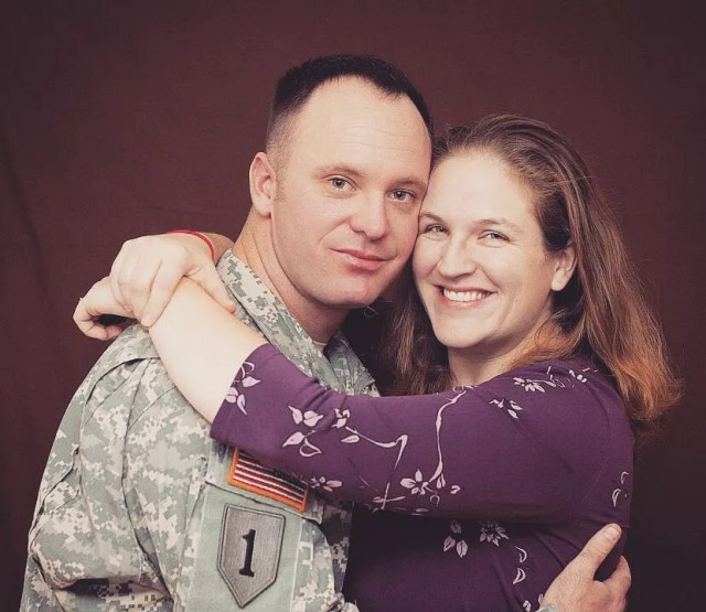 Military husband hugging his wife in front of purple backdrop. Photo by Instagram user @soldierswifecrazylife