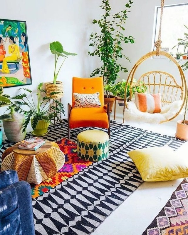 Living room designed in Eclectic style with patterned rug and orange chair and tall house plants. Photo by Instagram user @bohemianhomedecor