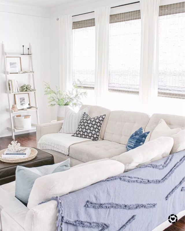 White living room with blue blankets and blue pillows decorated in Coastal style. Photo by Instagram user @caitlinmariedesign