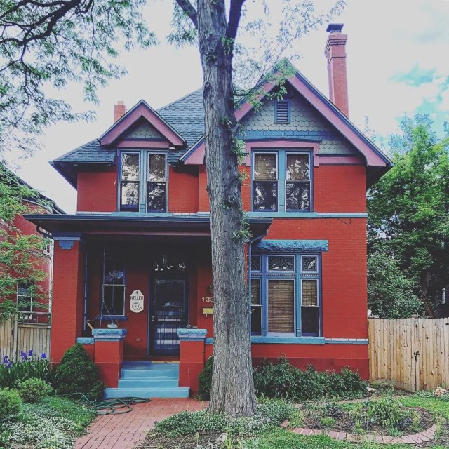 Two story home painted red with blue trim in Congress Park, Denver. Photo by Instagram user @grantrstevens