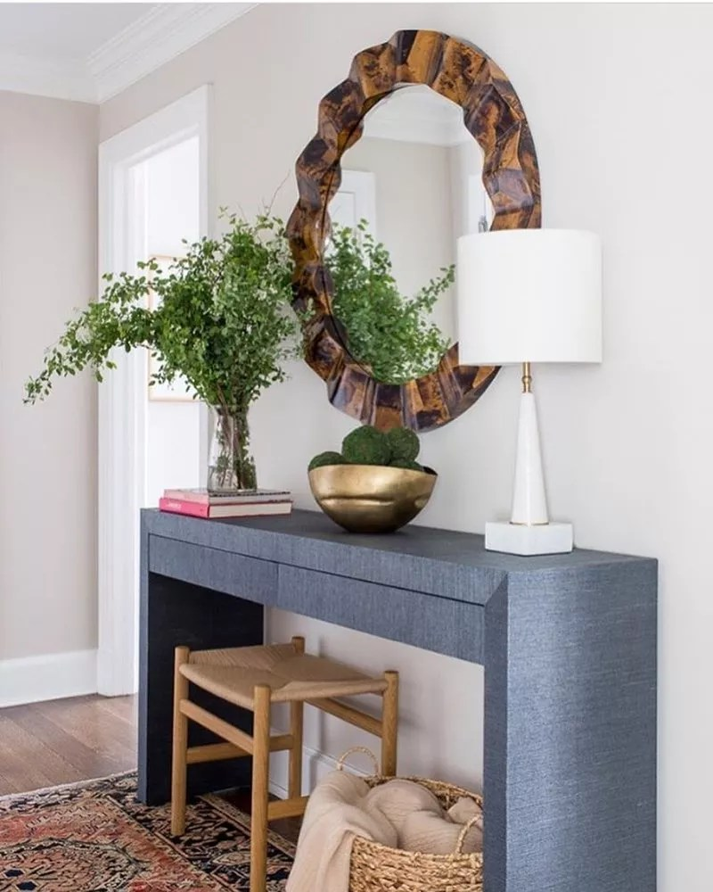 Round wood mirror above gray table in hallway with lamp and plant on top of it. Photo by Instagram user @livenupdesigns