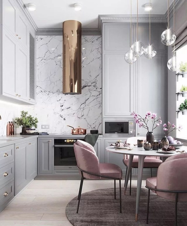 Kitchen with light gray cabinets and velvet pink chair. Photo by Instagram user @marieburgos.design