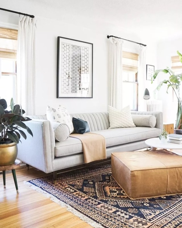 White living room with big windows and a gray couch. Photo by Instagram user @christalowryrealestate