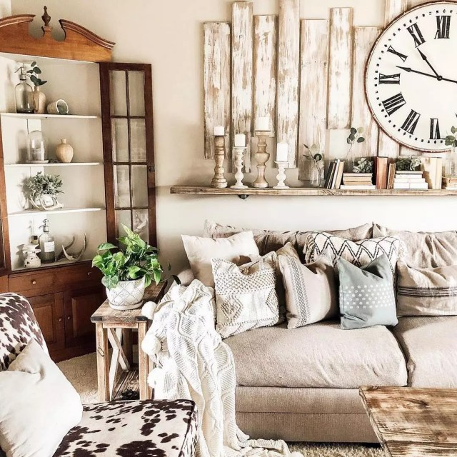 Living in Rustic style with gray couch and patterned pillows with worn wood on the wall. Photo by Instagram user @vintagemarketdayscntrlnr