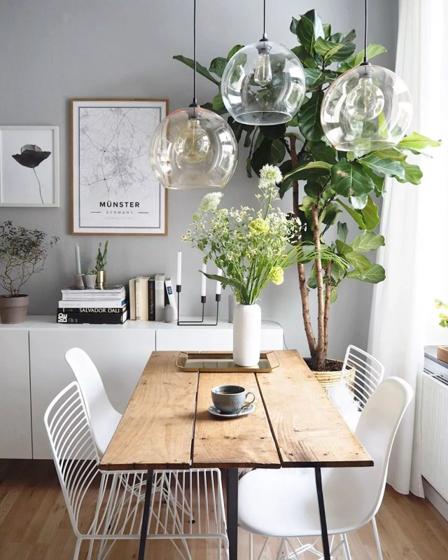 White dining room with wood table and tree in the corner designed by Scandinavian style. Photo by Instagram user @oursweetliving