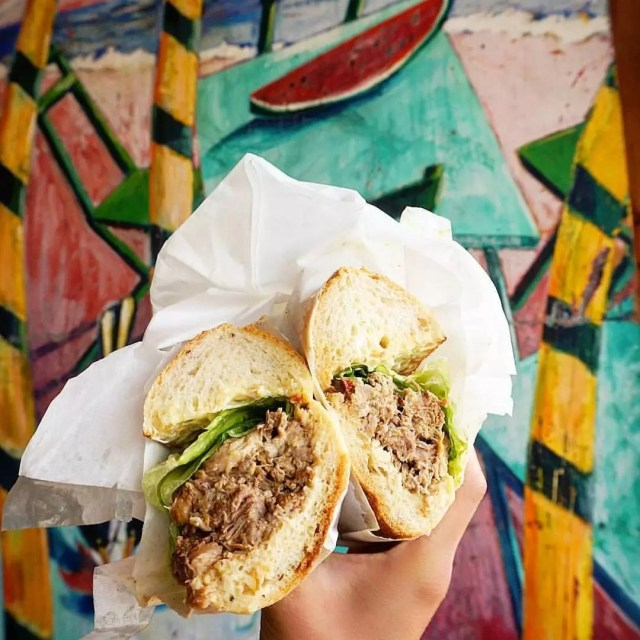 Beef sandwich in front of a mural at Un Bien in Seattle. Photo by Instagram user @bacontreesburger