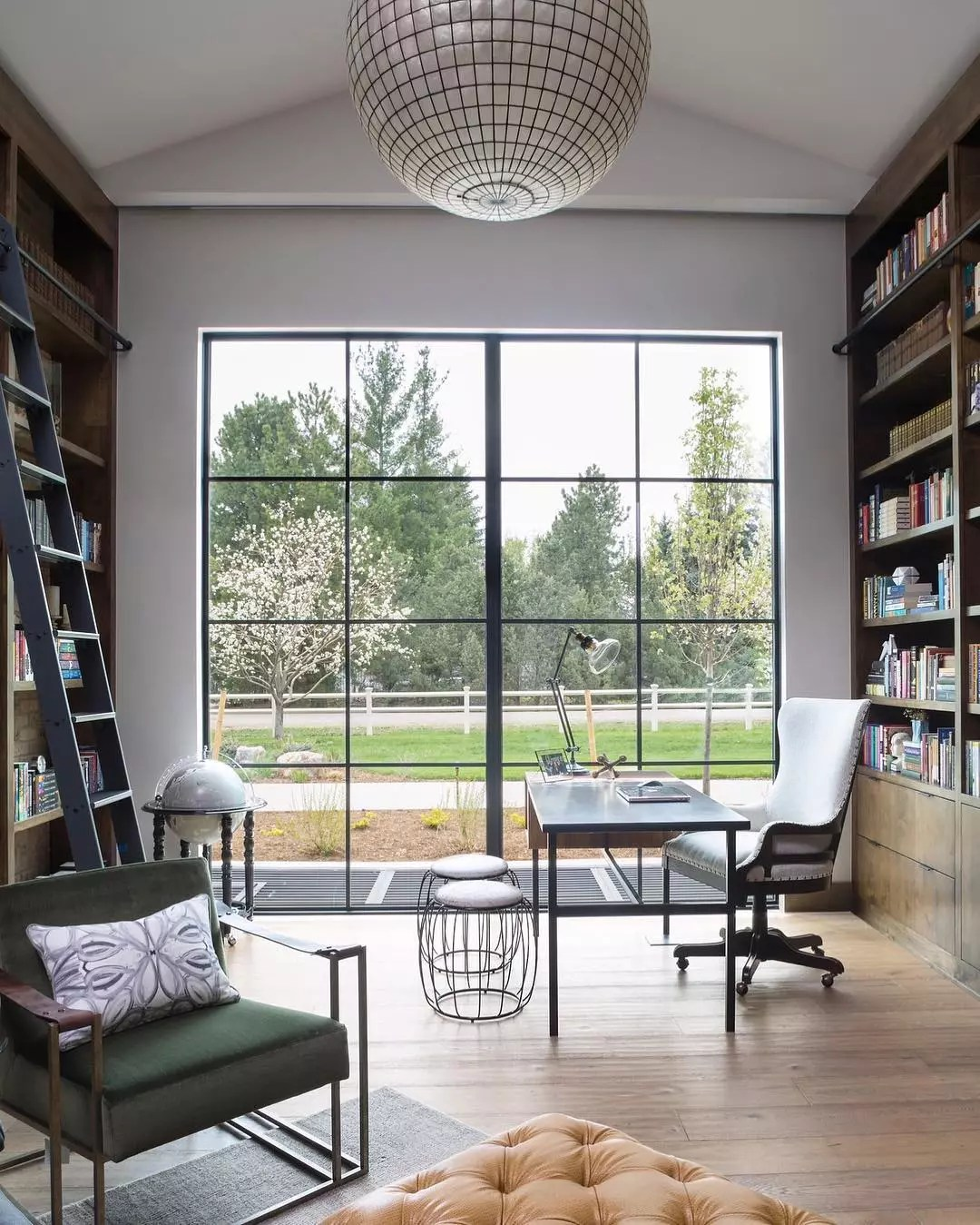 Home office with big windows and large bookcases and wire stools. Photo by Instagram user @duetdesigngroup