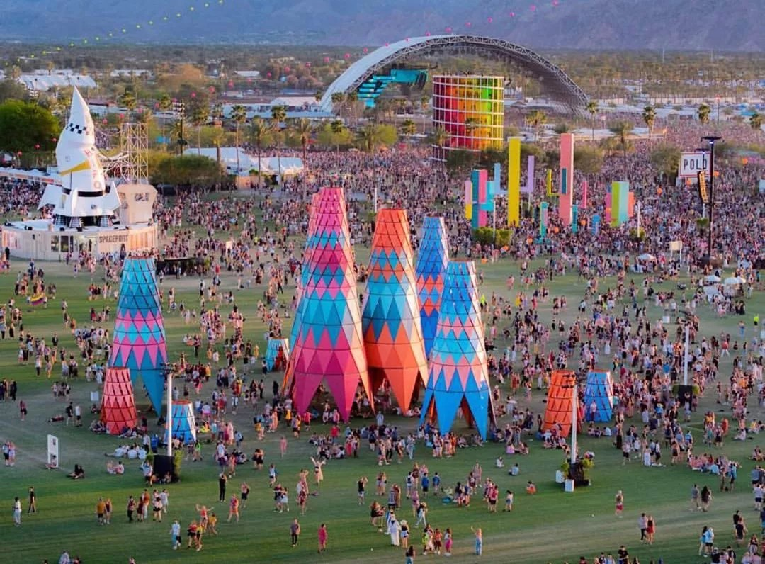 Tall colorful sculptures and music stages at Coachella festival. Photo by Instagram user @whiteowlaerial