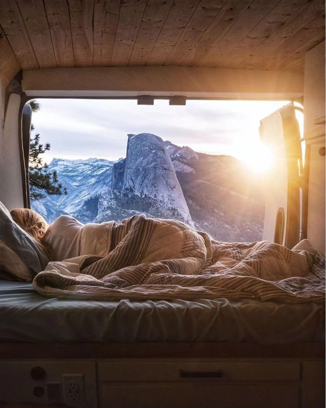 Girl laying in her van looking out the back at the mountains. Photo by Instagram user @jess.wandering