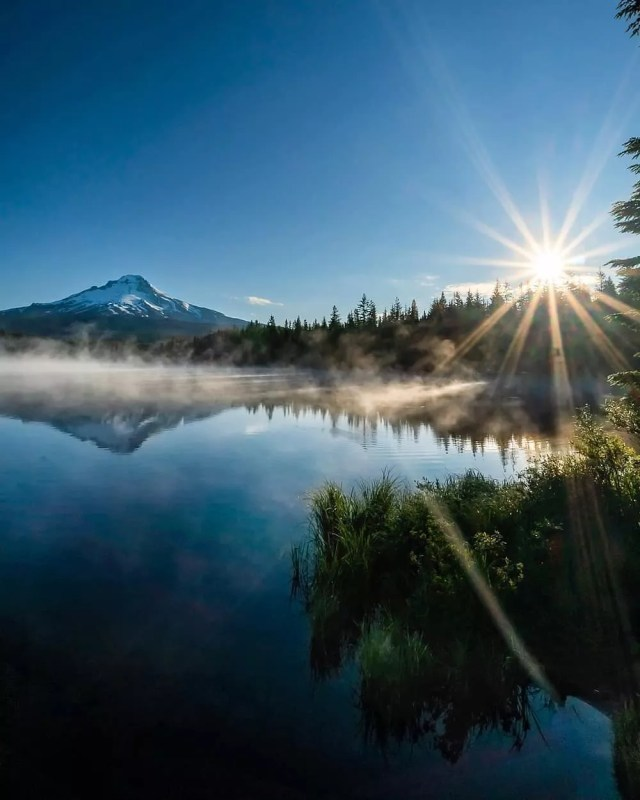 Sun shining over crystal clear lake with mountains in the back at Mt Hood National Forest, OR. Photo by Instagram user @browneyedsmile808