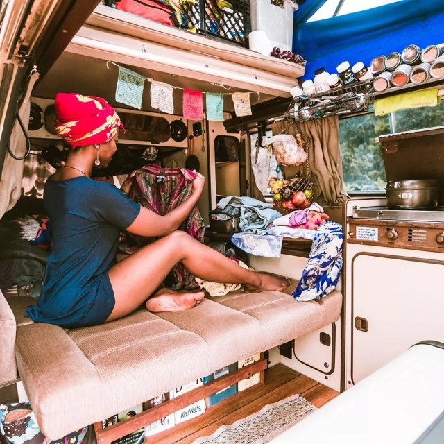 Woman folding her clothes in a van. Photo by Instagram user @irietoaurora