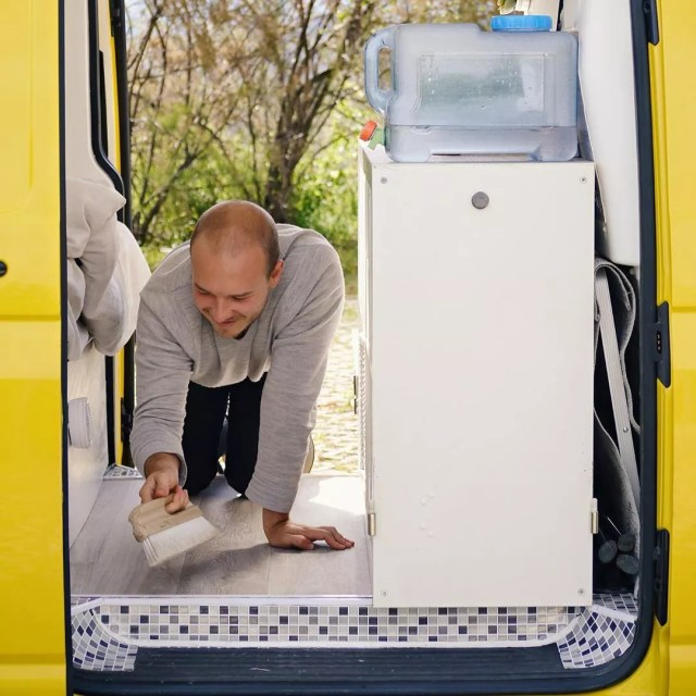 Guy cleaning the floor of van. Photo by Instagram user @ausgevandert