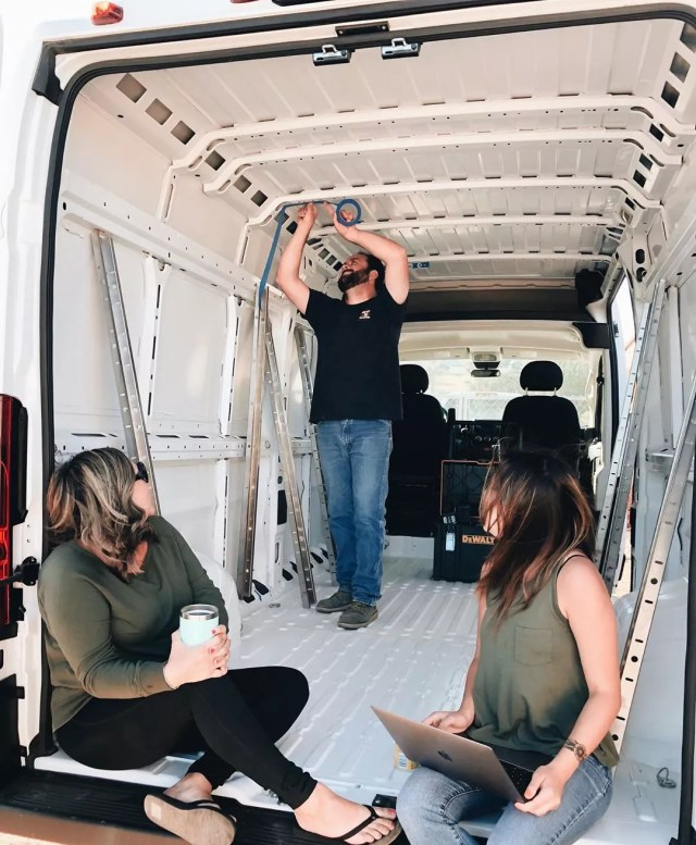 Man and two women fixing the inside of a van. Photo by Instagram user @losthiway_customs