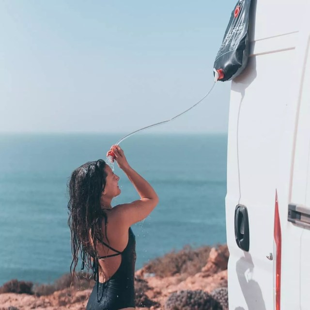 Girl showering in her swimsuit outside of her van. Photo by Instagram user @salty.roamers