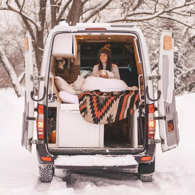 Girl sitting in the back of a van in winter. Photo by Instagram user @rebeccamoroney