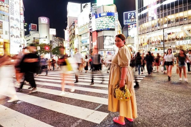 Girl standing in the middle of crosswalk in Tokyo. Photo by Instagram user @fracosma
