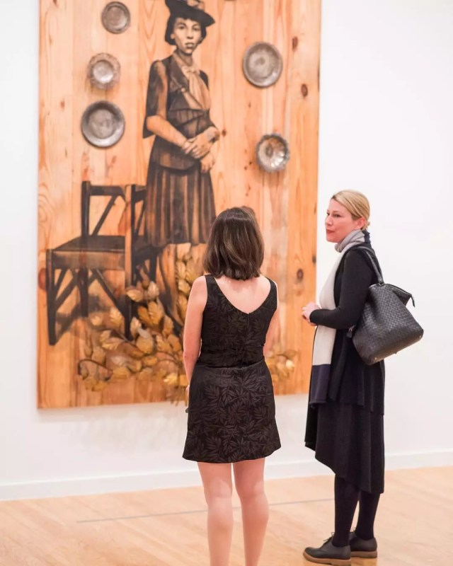 Two women looking at a wood painting. Photo by Instagram user @bhammuseum