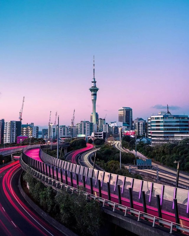 Tall buildings in Auckland, NZ with a purple sunset. Photo by Instagram user @vhthomas