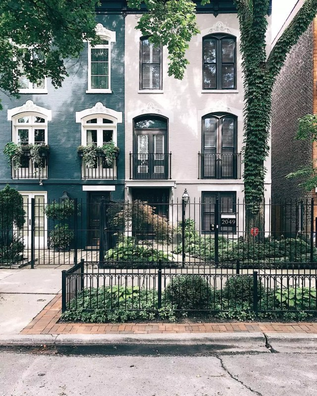 Dark green rowhouse next to a white rowhouse with black fence in front. Photo by Instagram user @_kateflores