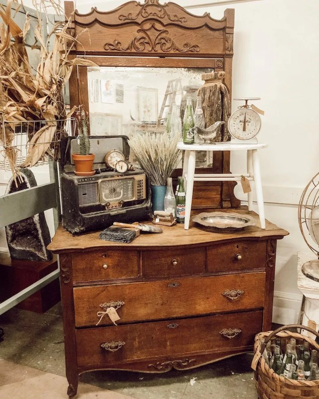 Old brown dresser with antique radio and stool on it. Photo by Instagram user @wattsandcogvl