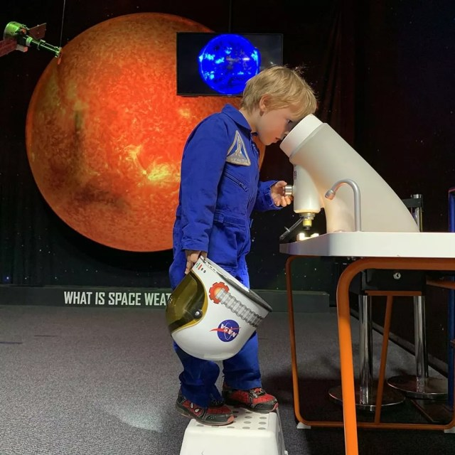 Little boy looking into a telescope in space outfit. Photo by Instagram use @spacefoundation