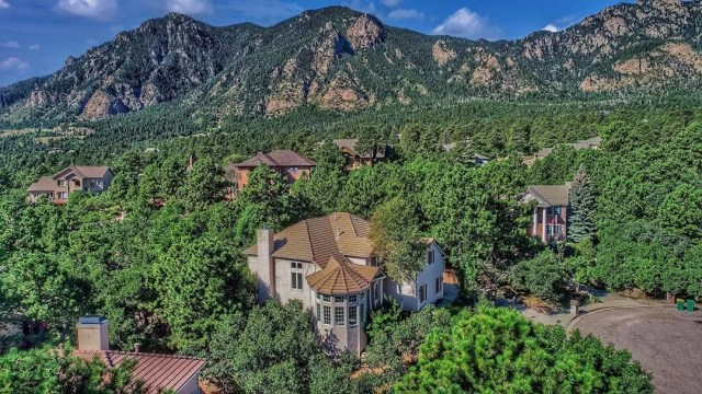A brown home surrounded by trees and mountains. Photo by Instagram user @coloradosprings.homes